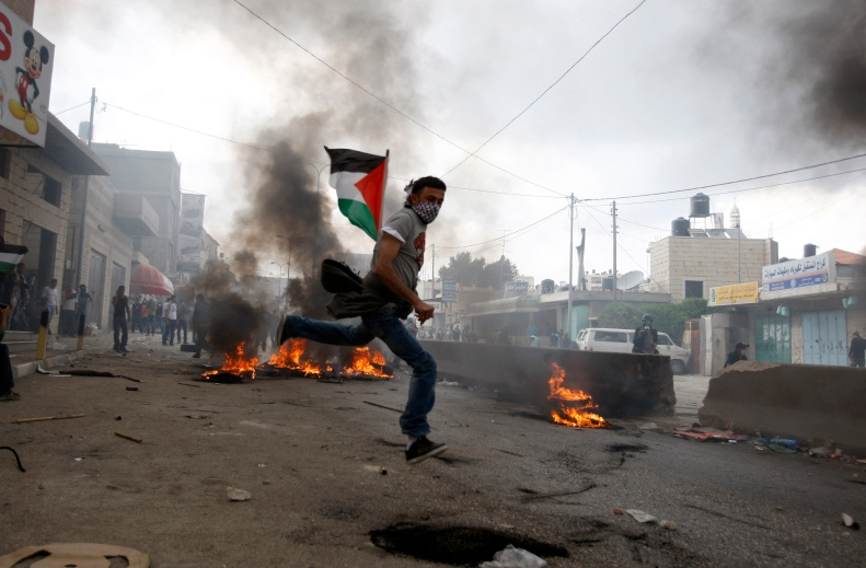 A Palestinian protester throws a stone at Israeli security forces during clashes at Qalandiya checkpoint